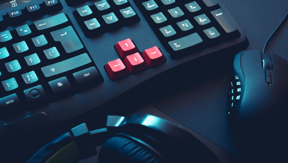 gaming keyboard, headphones and mouse on black table